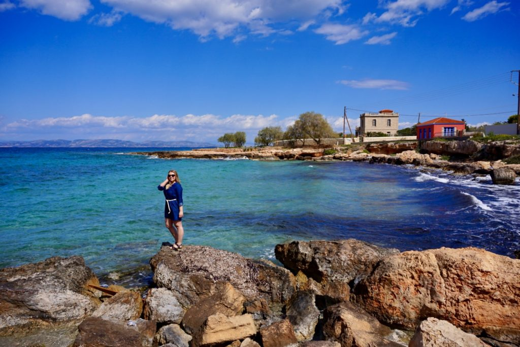 Sophie standing on some rocks in front of the turquoise-blue ocean. Located on the coast of the Greece island, Aegina.