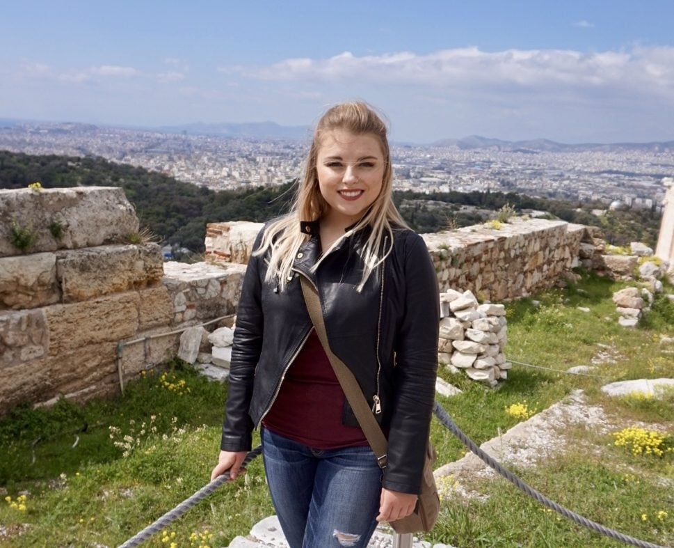 Sophie standing in front of ruins on the Acropolis historical site in Athens.