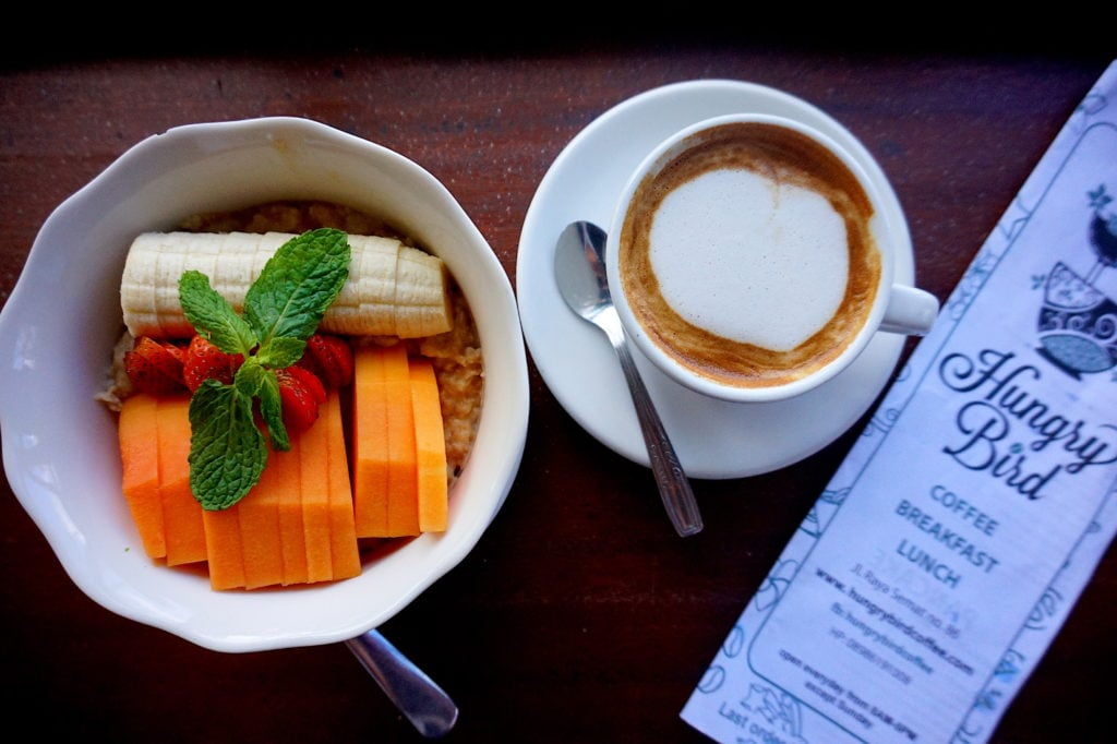 Hungry Bird Coffee Cafe's oatmeal bowl with fresh fruit and a coconut latte as a side.