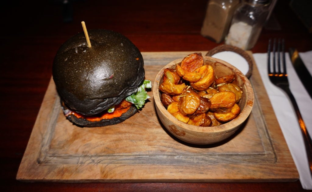 Nude Canggu vegan burger with a black charcoal bun and a side of crispy roasted rosemary potatoes (my favorite!).
