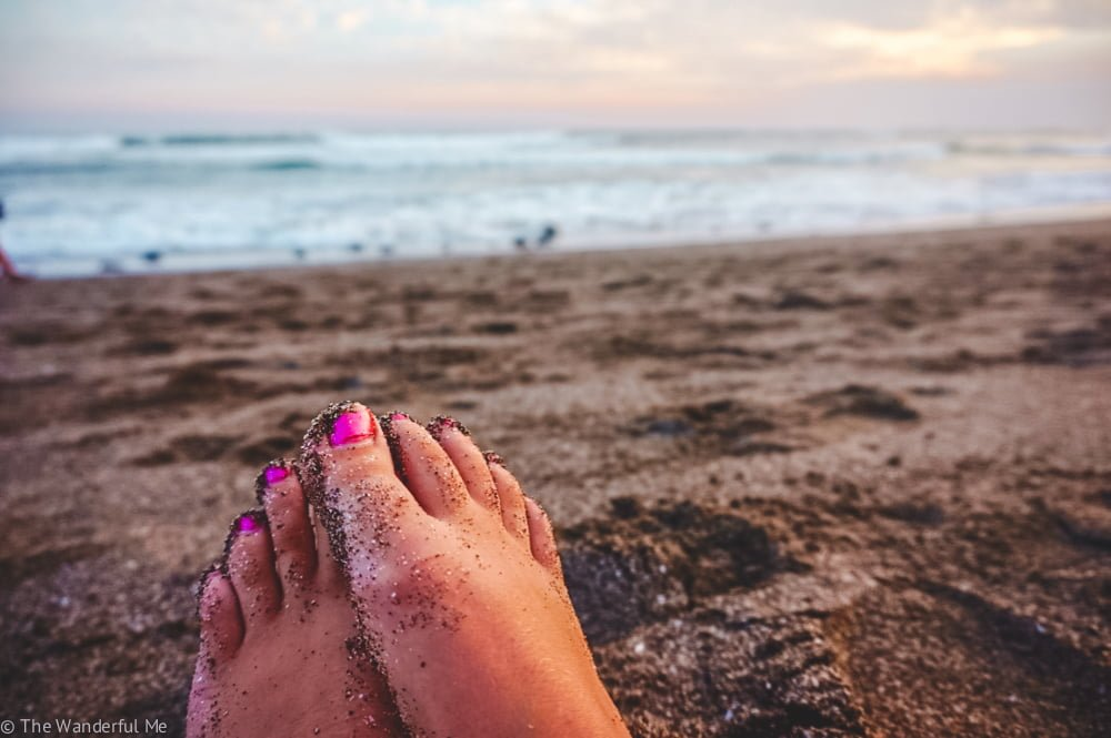 Sophie's feet covered with sand while sitting on the beach watching the Bali sunset.
