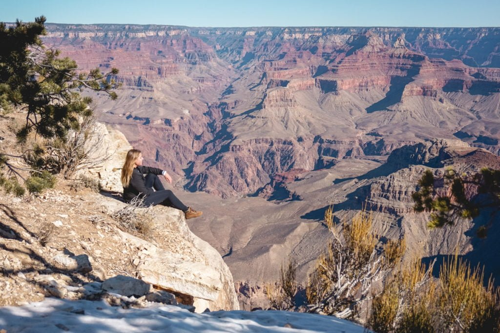 Sophie sitting on a ledge at the Grand Canyon National Park, a must visit attraction on any Arizona itinerary.