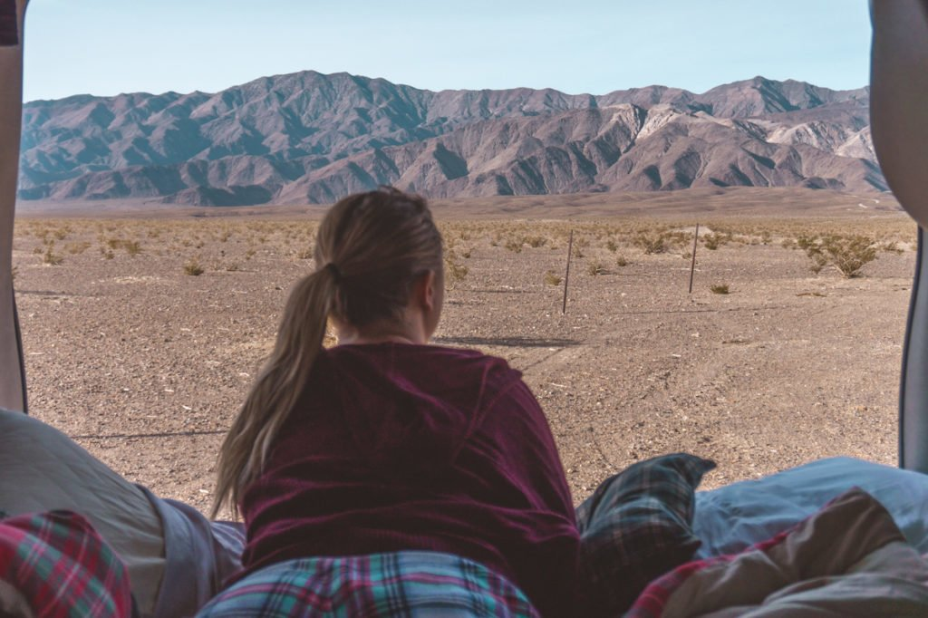 Sophie laying in the back of her road trip van and looking out at Death Valley National Park.