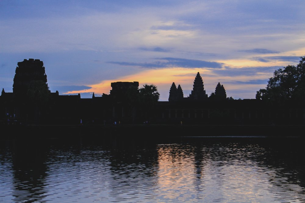 Pathetic colors glistening over the beautiful Angkor Wat temple complex. • Angkor Wat Sunrise - The RIGHT Way to Do it + My Personal Experience