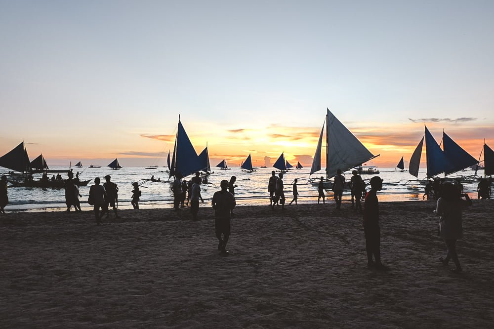 Hundreds of tourists on the beach in Boracay, forcing the government to restrict travel.