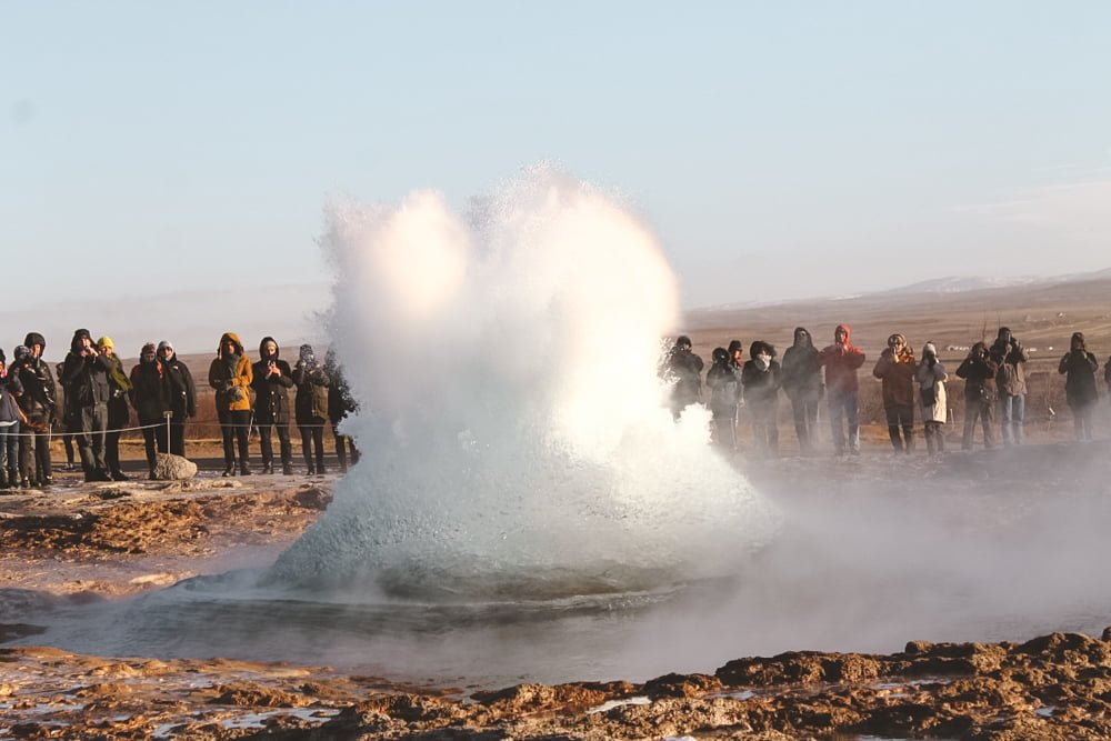 A popular geyser in Iceland, surrounded by hoards of tourists.