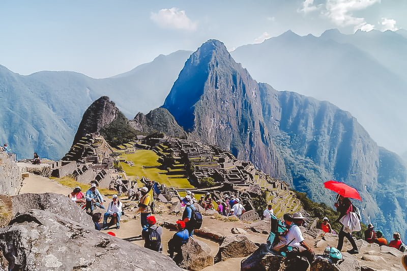 Crowds of tourists and travelers gather at the top of Machu Picchu to see the remarkable site for itself.
