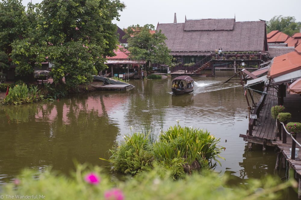 A boat jets down the man-made floating market waters.