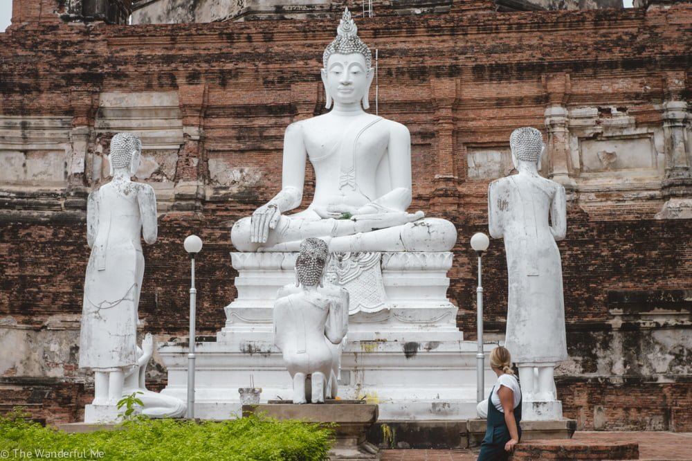 Sophie sitting in front of four Buddha statues, admiring the shimmering white carving and detailing.