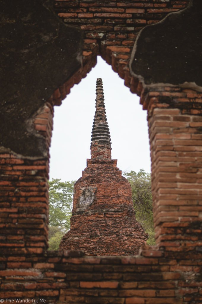 Looking through a crumbling temple window at a Chedi.