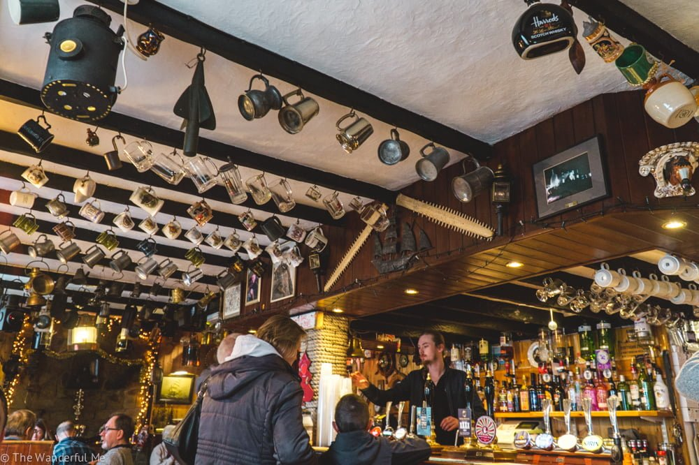 Ty Coch Inn pub has old mugs hanging on a rafters! Such a unique pub to explore in North Wales.