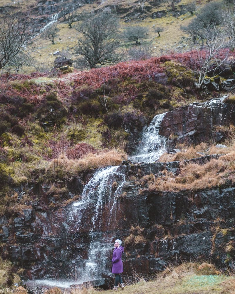 Sophie standing in front of an incredible waterfall in Brecon Beacons National Park.