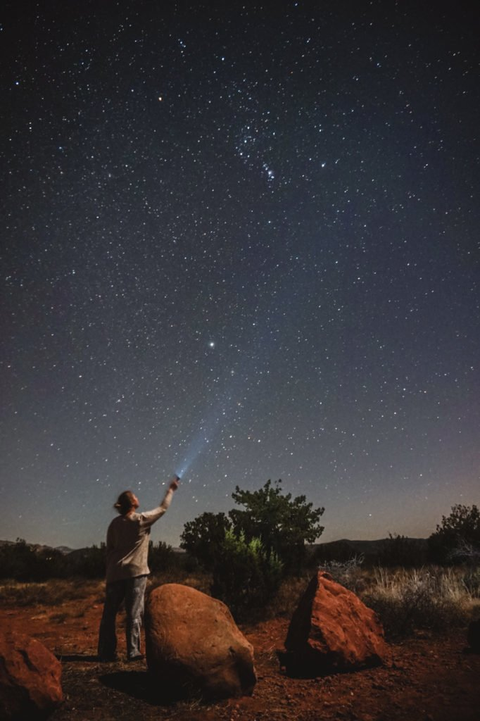 Standing in the middle of a red rock landscape, shining a flashlight up at the glittering stars.