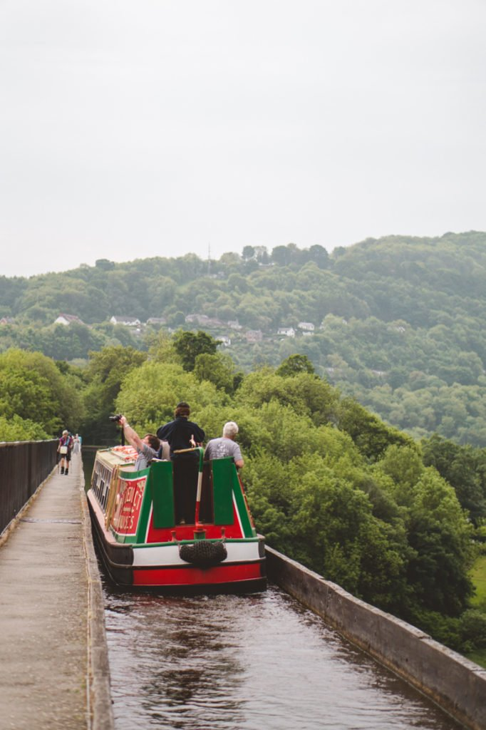 A green and red canal boat making its way across one of the many aqueducts in Wales.