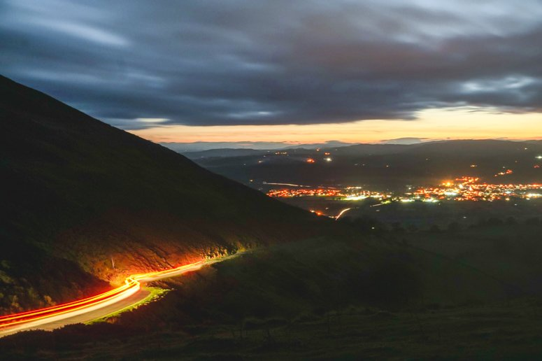 Nighttime views in North Wales with car lights streaking down the side of a mountain.