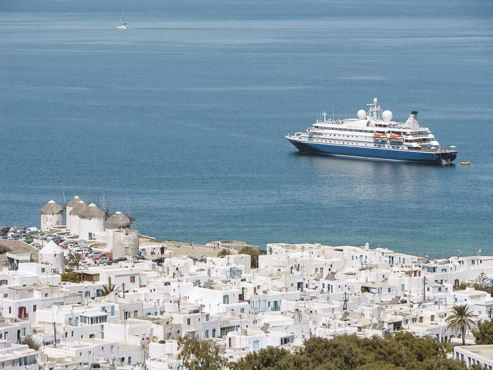 A cruise ship waits out at sea just off the coast of a Greek island.