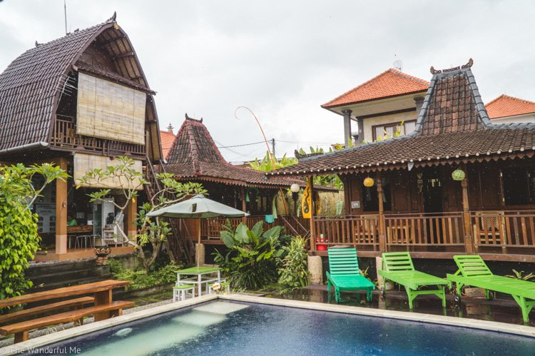 Hostel in Bali with a pool, sun chairs, and a relaxing atmosphere.