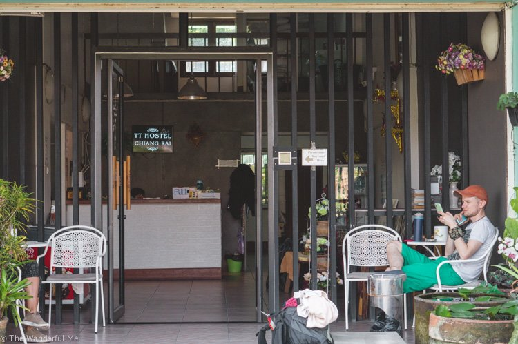 Dan sitting in front of a hostel in Chiang Rai, Thailand. Hostels are a great place to stay to save money when backpacking Southeast Asia!