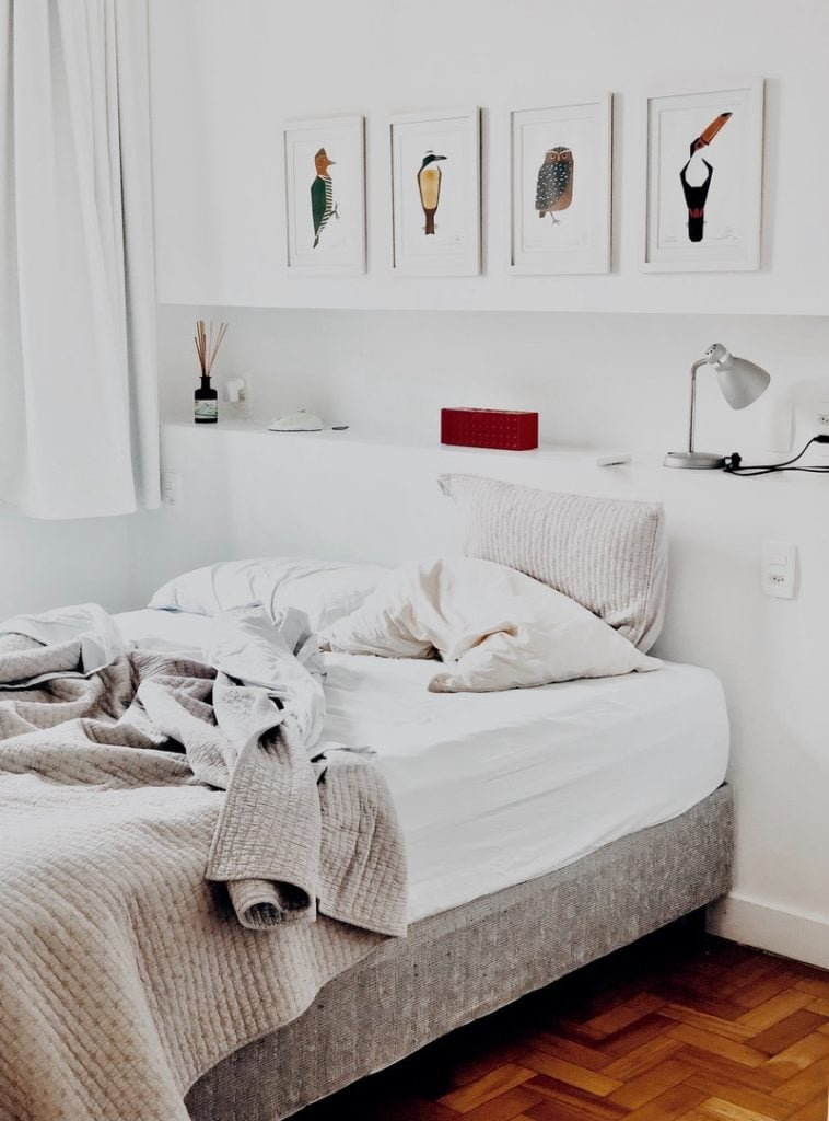 A comfy white bed with three cushy pillows and some decorative items behind it, like a few paintings and a lamp.