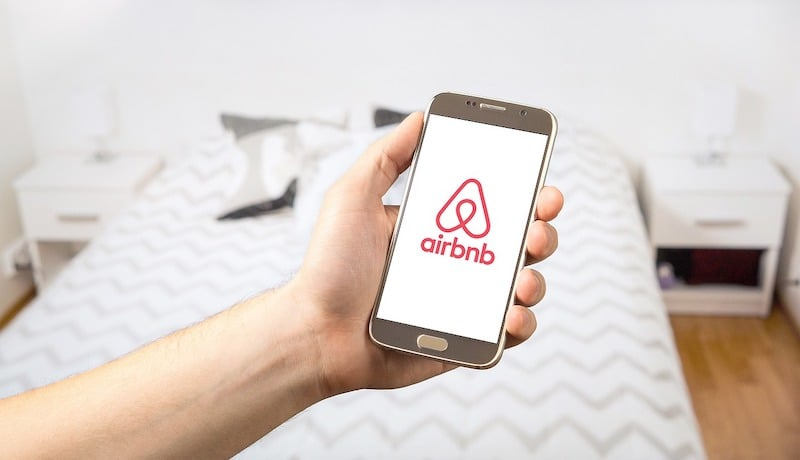 The Airbnb logo on a phone screen being held by a hand in what looks to be an rented out apartment on Airbnb.