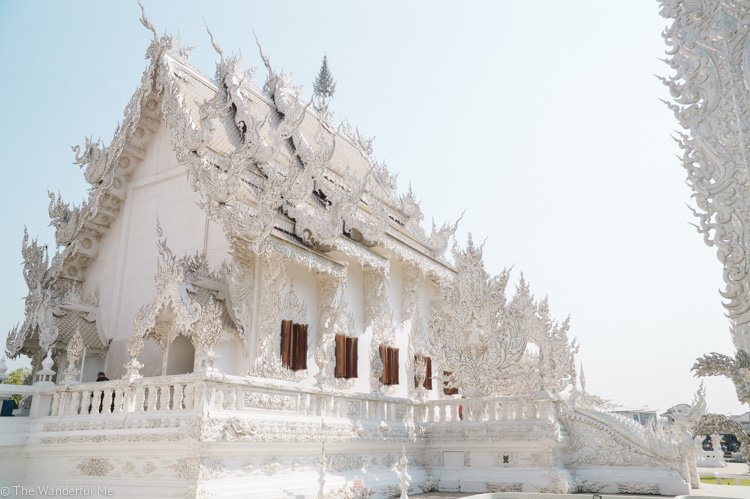 The White Temple shining in the morning sun with clear blue skies behind it.