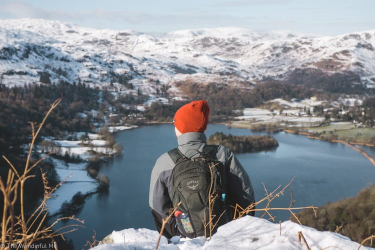 Dan sitting in the Lake District with far-off mountains in the distance. He's wearing an Osprey Daypack, which is an essential item for a road trip.
