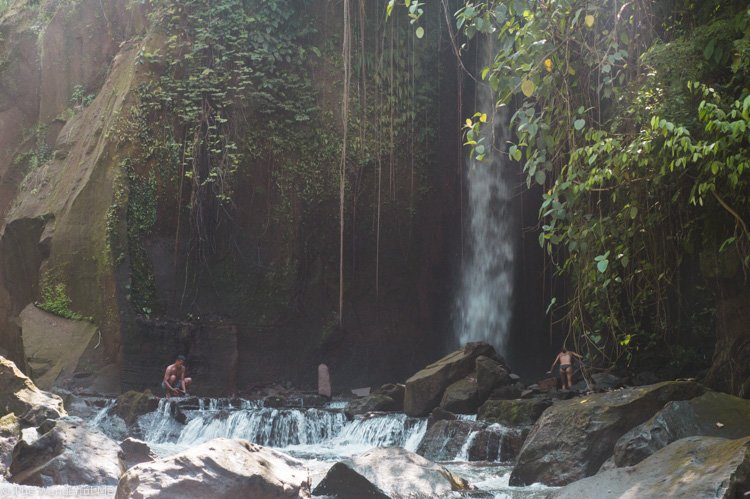 A cascading waterfall surrounded by large rocks and lush jungle.