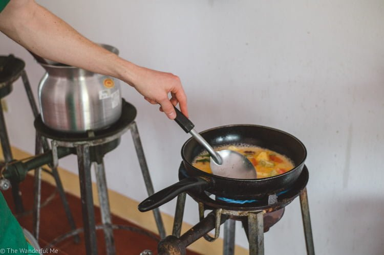 Cooking up curry in a big kettle over a roaring gas stove.