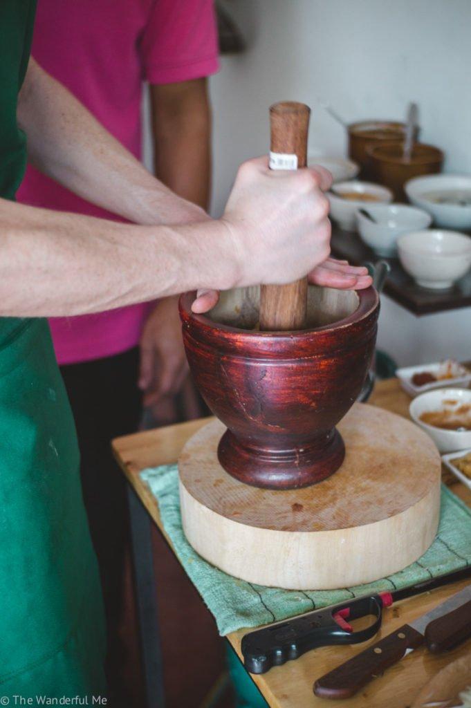 Dan crushing papaya in a pestle and mortar.