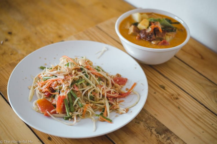 Vegan papaya salad with vegan duck curry in the background.
