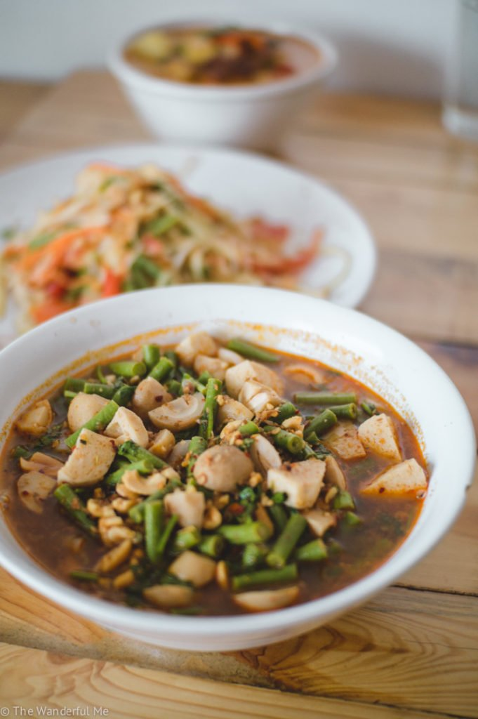 Tom Yum soup with papaya salad and vegan duck curry in the background.