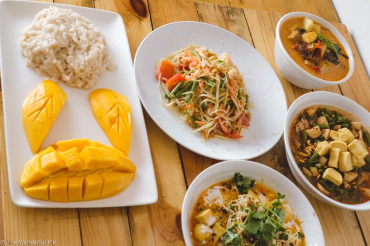 A spread of vegan yumminess; mango sticky rice, papaya salad, khao soi, tom yum soup, and vegan duck curry.