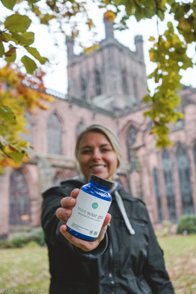 Sophie standing in front of a cathedral holding up the bottle of Ora Organic trust your gut probiotics, a top brand for travel probiotics.