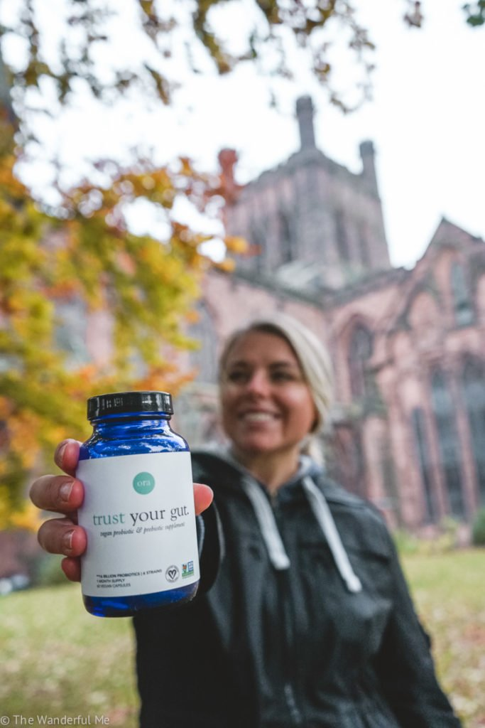Sophie holding up the Ora Organic trust your gut vegan probiotic and prebiotic supplements in front of the Chester Cathedral.