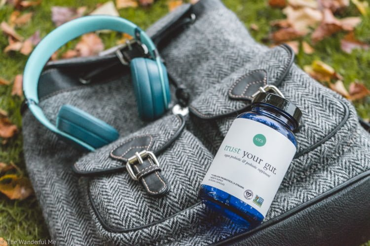 The Ora Organic Trust Your Gut probiotics bottle hanging out on top of Sophie's black and white backpack with a pair of blue headphones in the background.