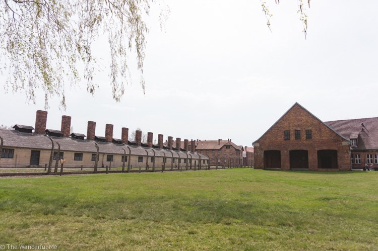 The fenced wall and one of the many cold brick buildings of the Auschwitz Concentration Camp, a must-visit attraction in Eastern Europe.