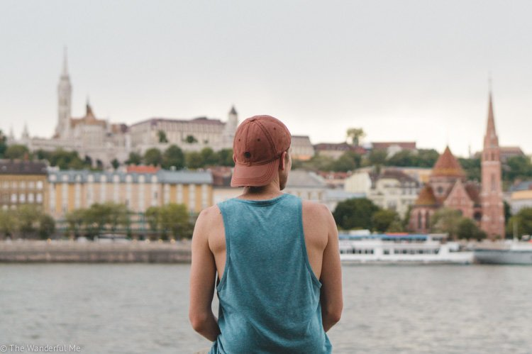 Dan, Sophie's boyfriend, sitting alongside the Danube in Budapest with Buda Castle in the background.