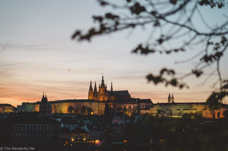 The beautiful city of Prague lit up at sunset with Prague Castle in the background.