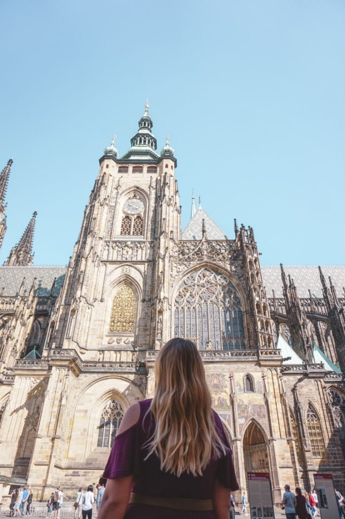 A towering church with gothic architecture, found in the Prague Castle neighborhood.