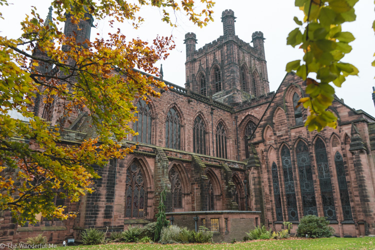 Chester Cathedral surrounding by lush orange, yellow, red, and green leaves in fall.