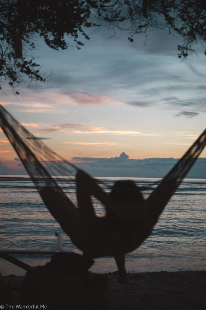 Someone laying on a hammock watching the sunset in Indonesia.
