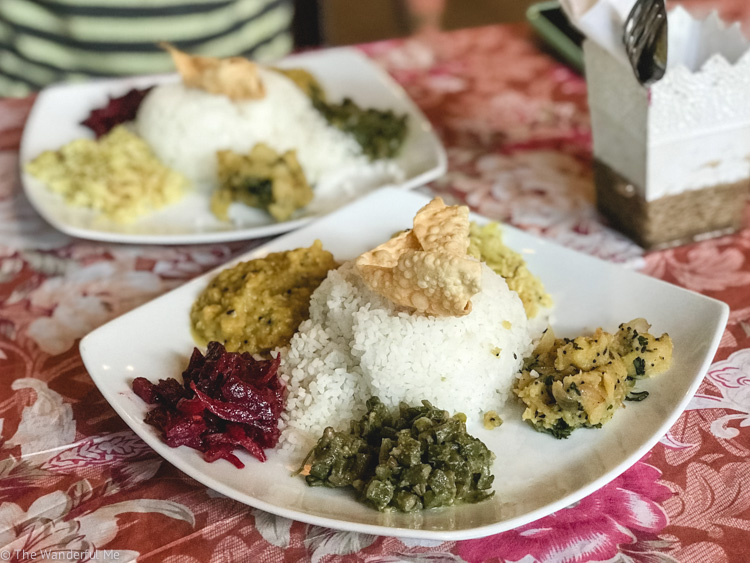 A plate of 5 different curries and sides with a hefty portion of rice topped with a fried papadom from the Matey Hut, a great place for vegans in Ella, Sri Lanka.