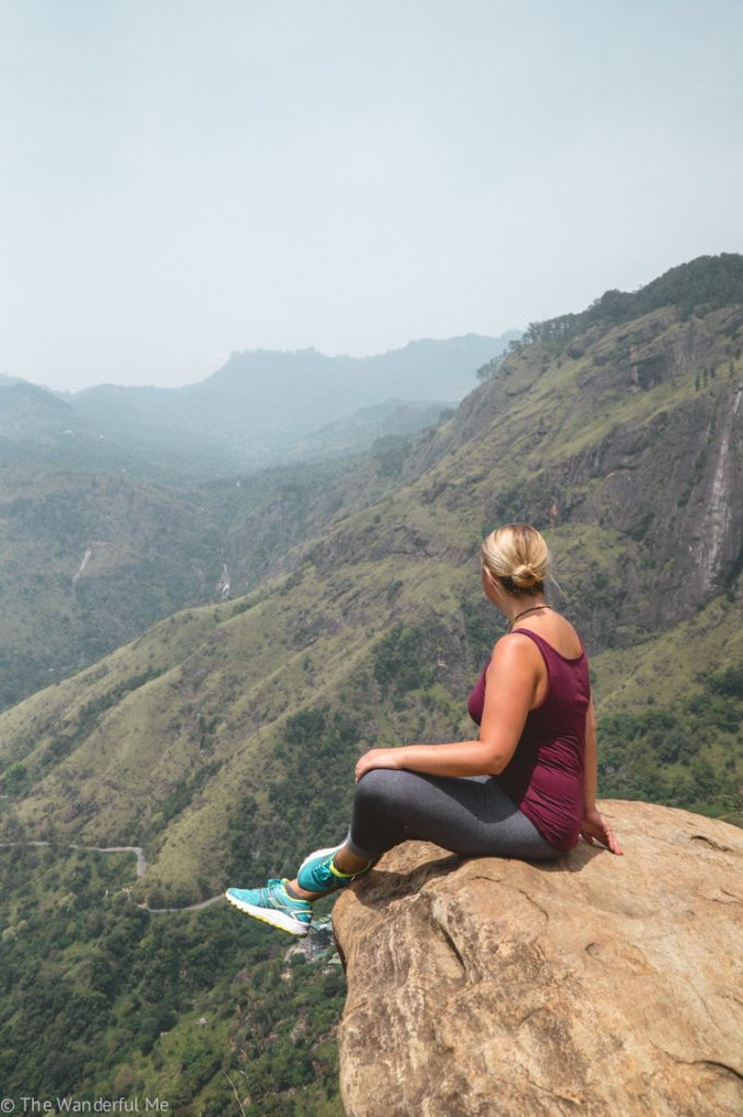 Sophie sitting on the edge of a rock on Little Adam's peak in Ella, Sri Lanka.