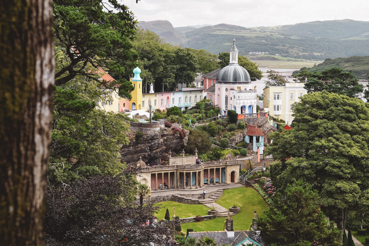 The Italian-style village of Portmeirion off in the distance with its Mediterranean-colored buildings and rolling green hills in the background.