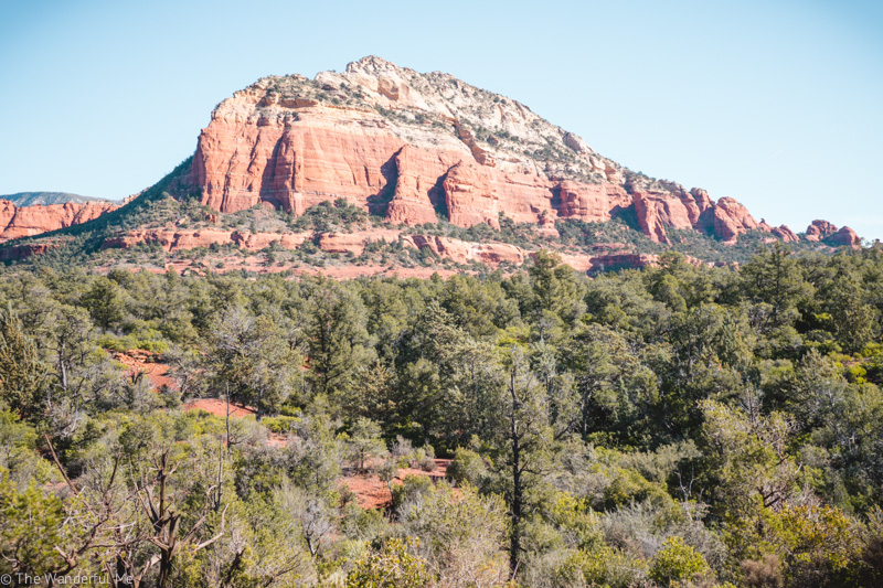 A towering red rock mountain surrounded by green trees and blue skies.