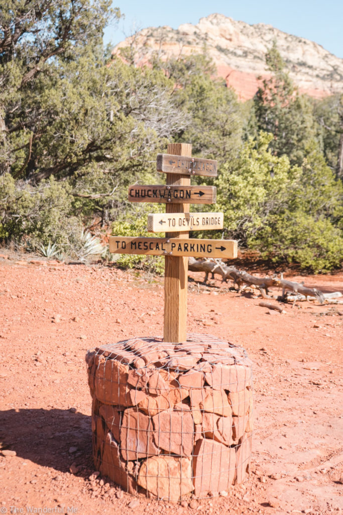 A signpost stating which way Devil's Bridge, Chuck Wagon Trail, and Mescal Parking is.