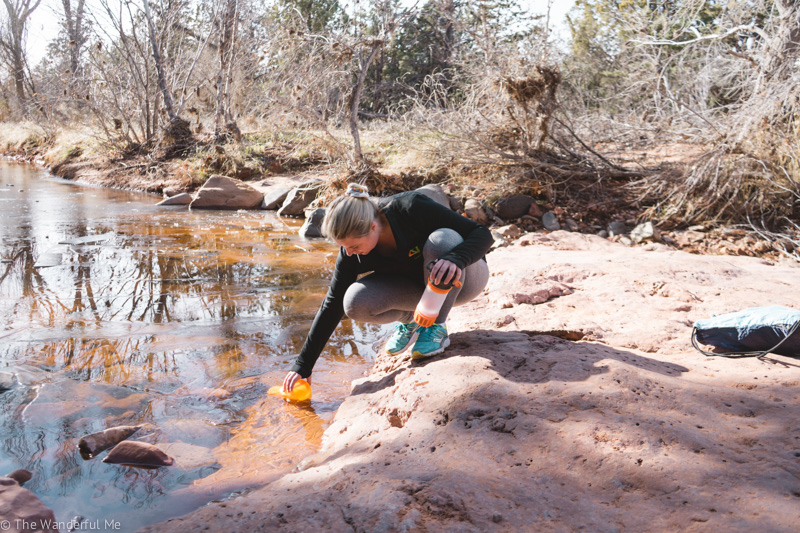 Sophie filling up her GRAYL filtering water bottle in a stream near Sedona, Arizona.