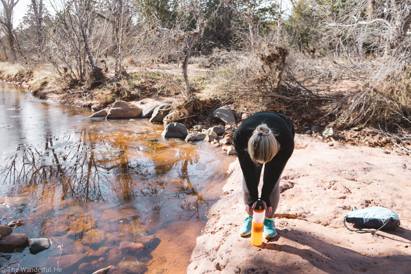 Sophie filtering river water while on the Devil's Bridge hike in Sedona.