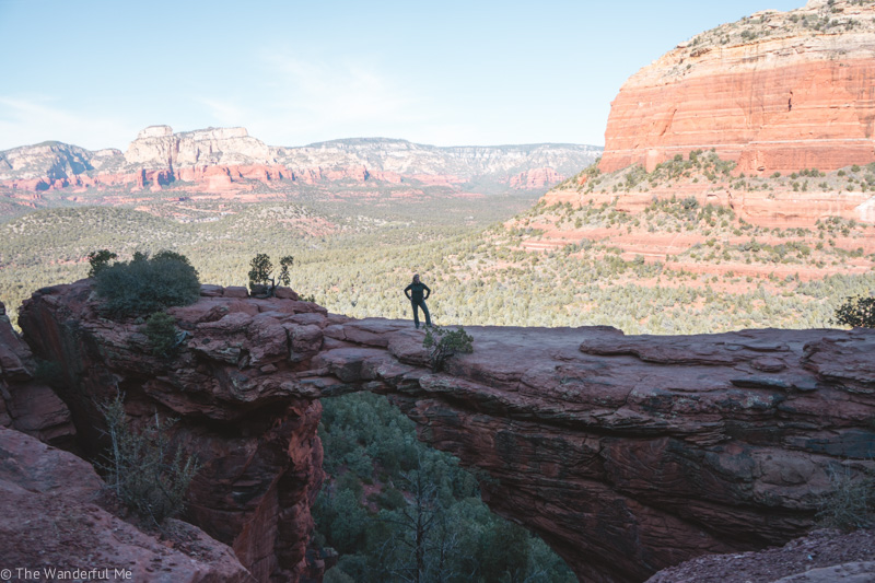 Sophie's mom standing out on Devil's Bridge with a gorgeous background of green trees and red rock mountains.