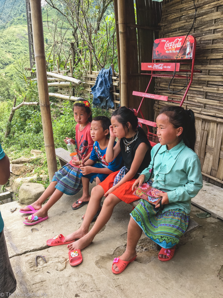 Four Sapa kids chilling out on a bench, looking tired in the Vietnam heat.